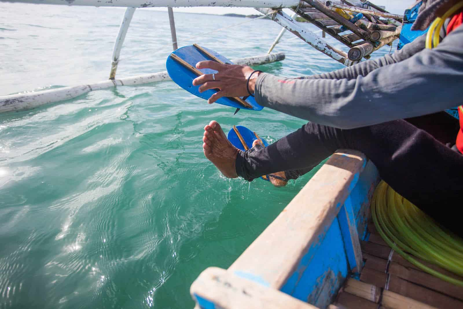 A man sits on the edge of a canoe putting on blue flippers.