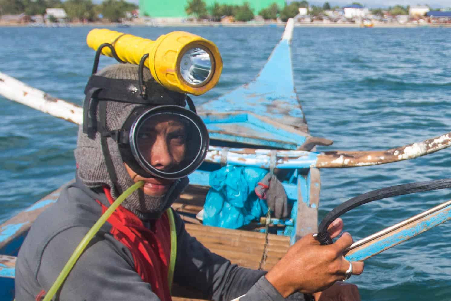 A man sits on a boat, with a swim mask on, a flashlight strapped to his head and a plastic tube in his mouth, ready to go pa-aling, one of the most dangerous jobs.