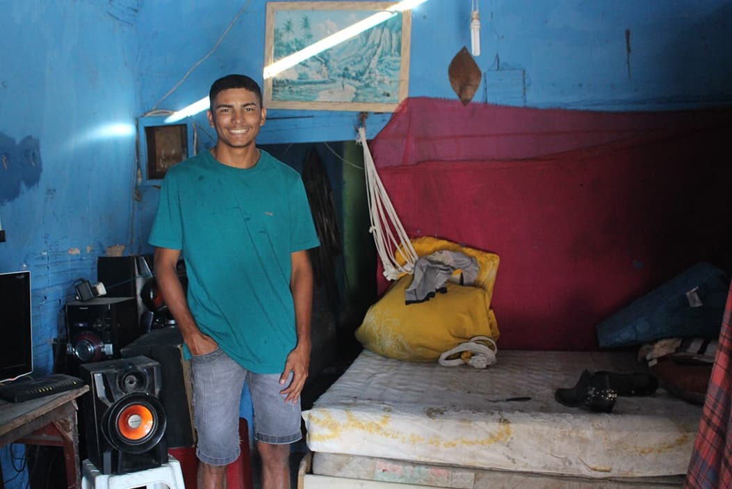 A young man in a teal shirt and jean shorts stands inside a blue room with a bed and stereo system next to him.