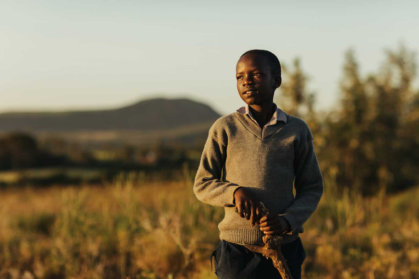 A boy wearing a grey sweater holding a wooden stick stands in the sunset in a field, looking into the distance.