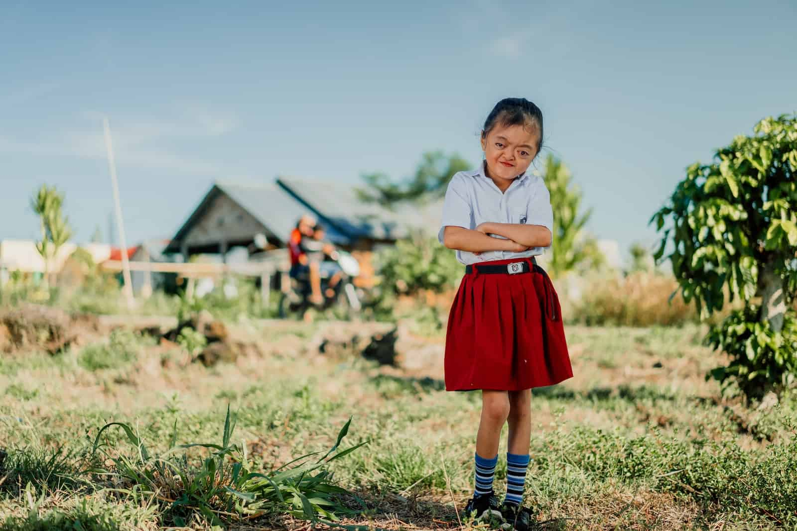 A photo of a girl with Apert Syndrome in a red and white school uniform stands in front of a house, with her arms crossed in front of her.