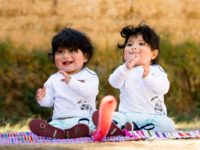 Two cute babies sit on a blanket, smiling