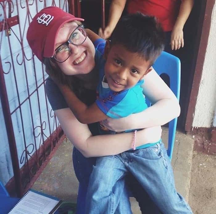 A girl in a red hat hugs a young boy as they sit in a chair.