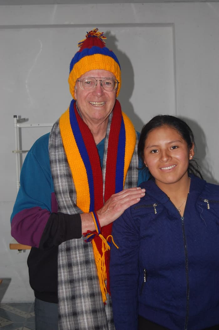 an older man wearing a colorful scarf and hat poses with a young man.