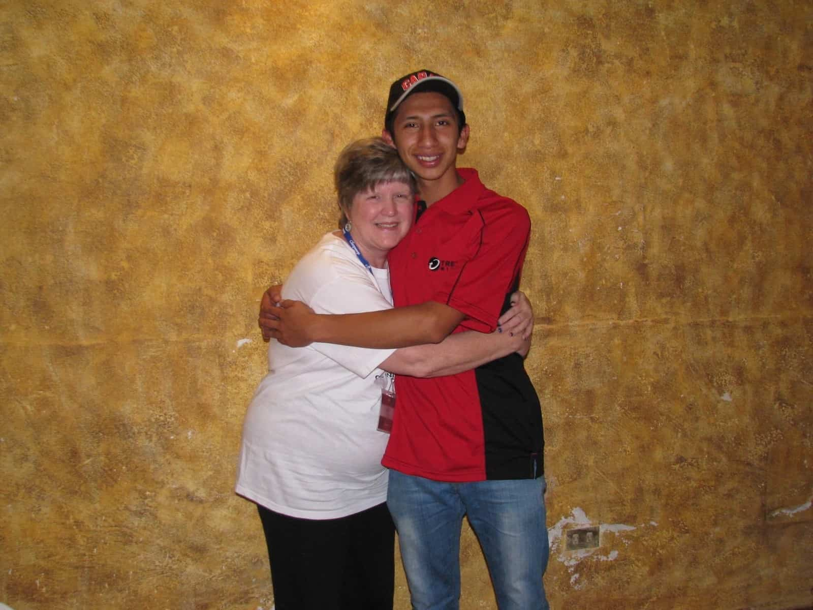 A woman in a white shirt and a young man in a red shirt hug one another tightly.