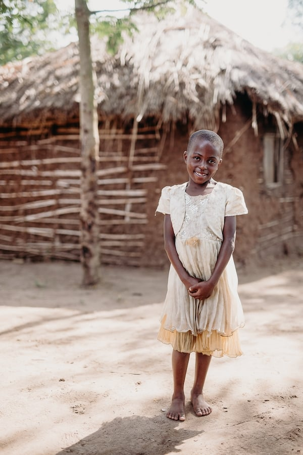 A girl in a white dress stands in front of a wood and mud thatched house.