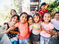 A group of children in Honduras smile for the camera.