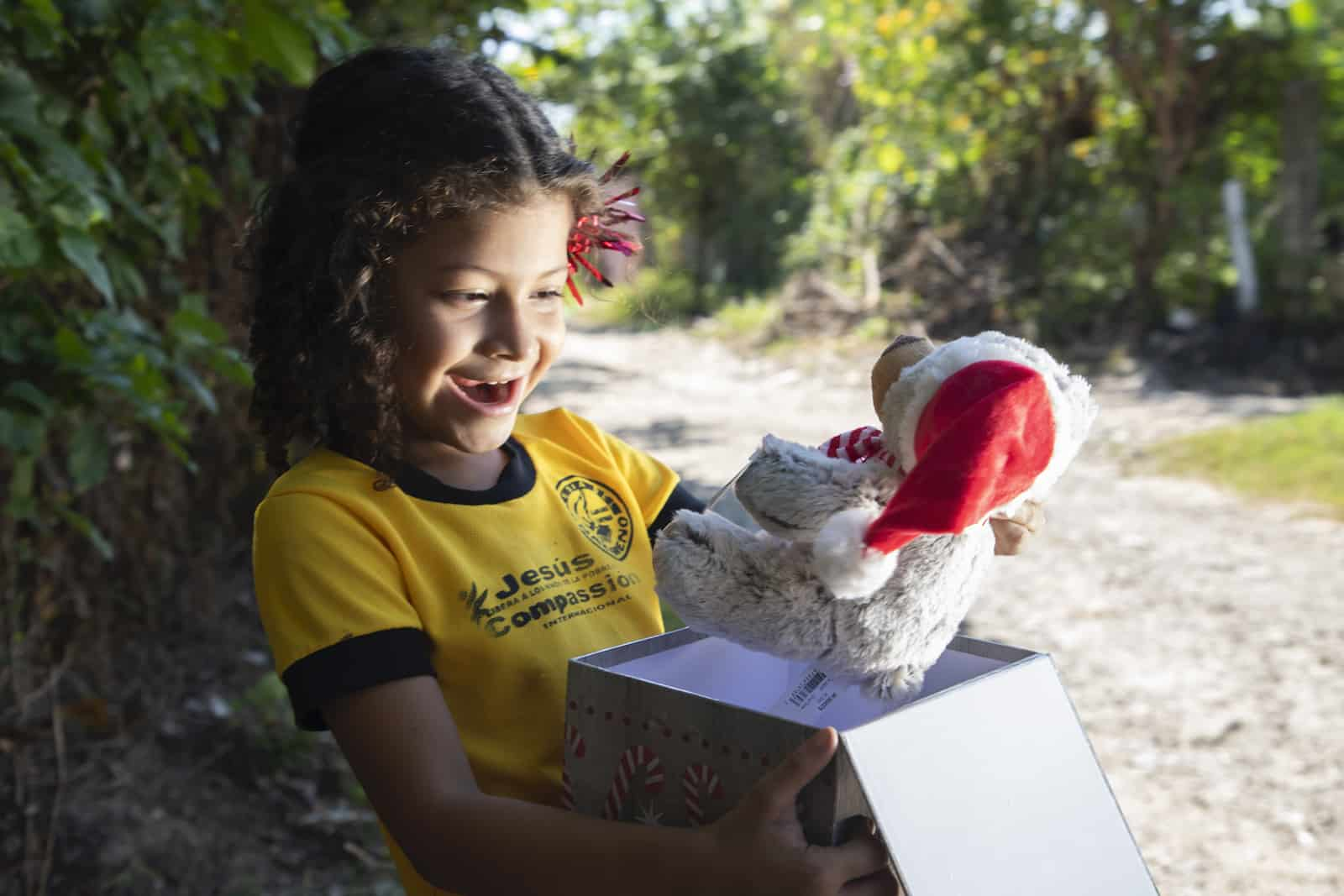 Christmas in El Salvador: A girl opens a gift with a teddy bear in it.