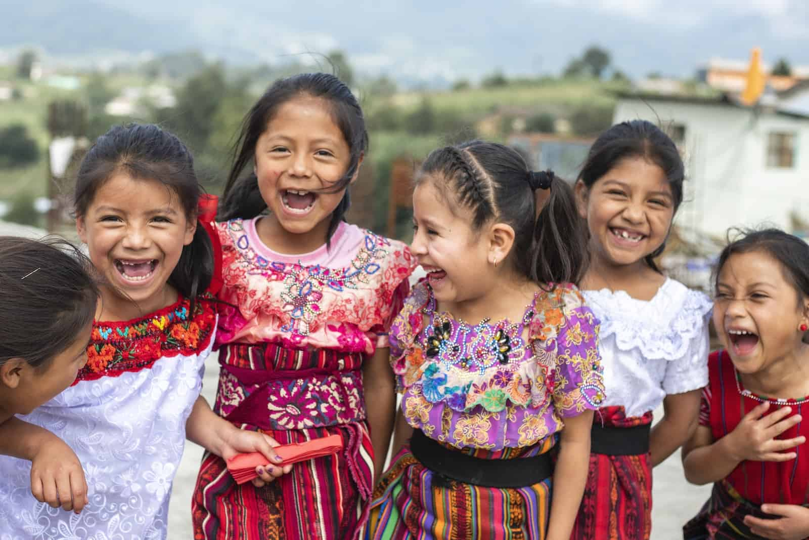 Girls in traditional Guatemalan dress laugh together