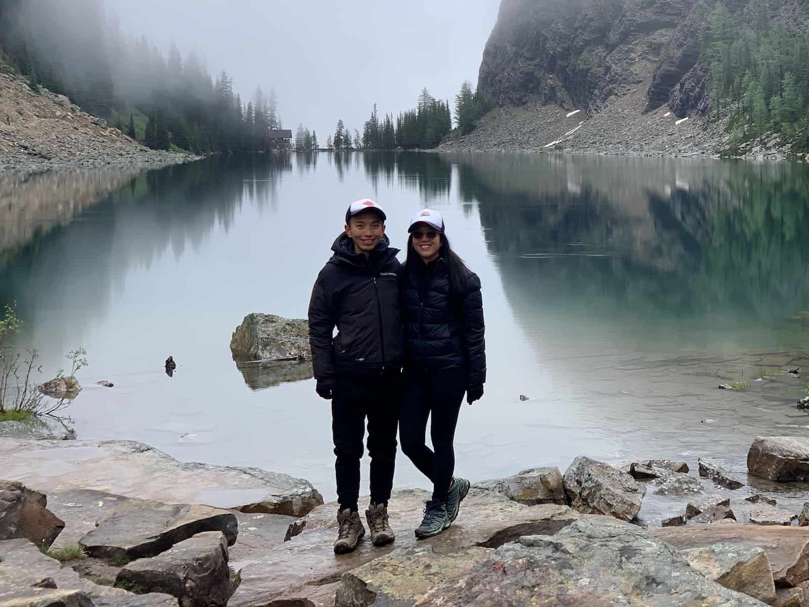 A man and woman stand in front of a mountain lake