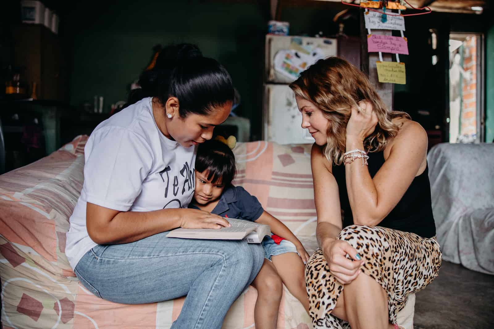 Two women and a girl read the Bible in a living room.