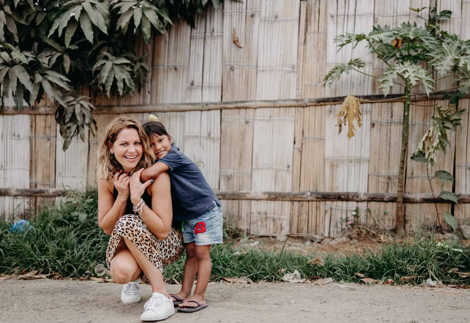Candace Cameron Bure squats on the ground, with a young girl hugging her.