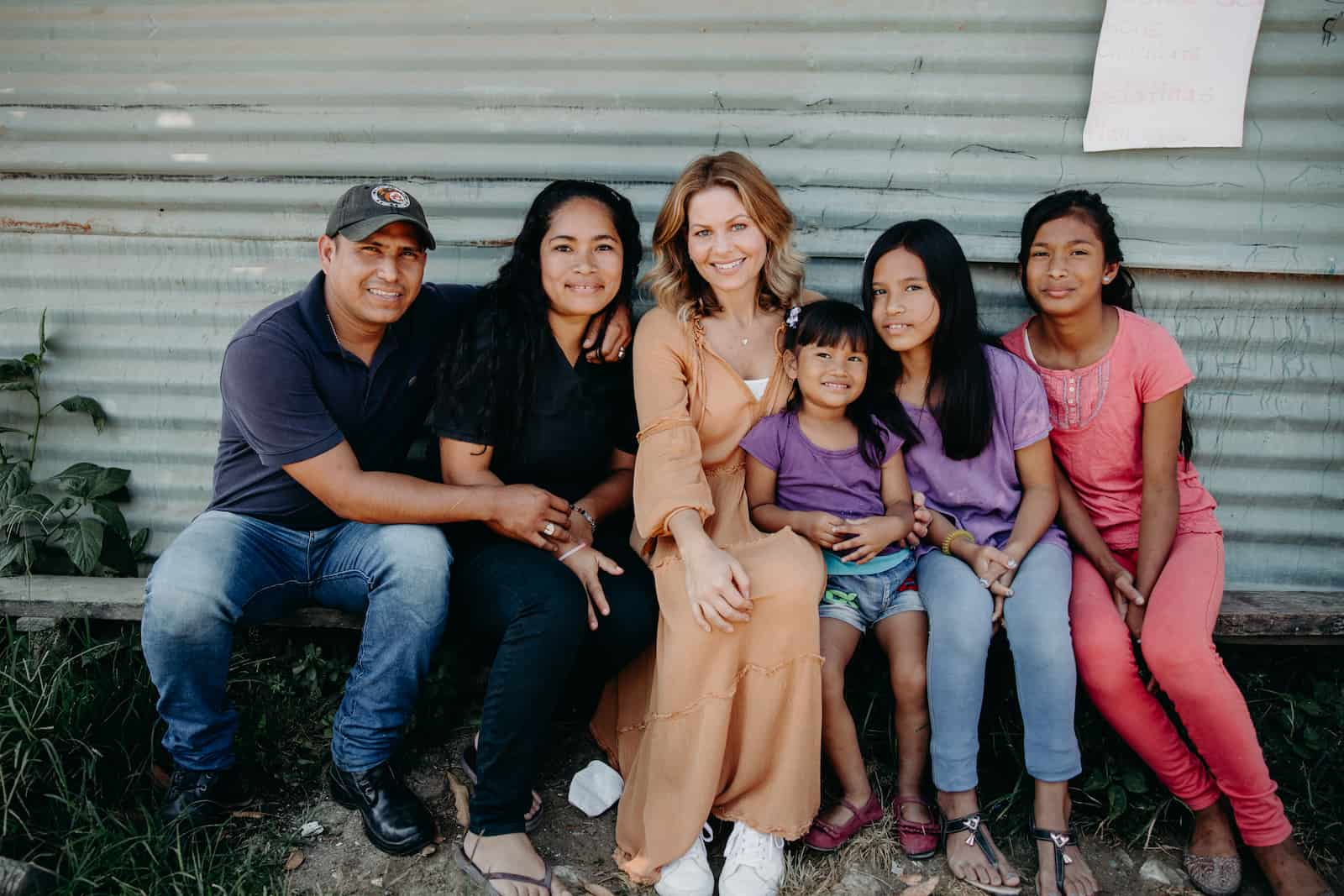 Candace Cameron Bure sits with a family with three girls.