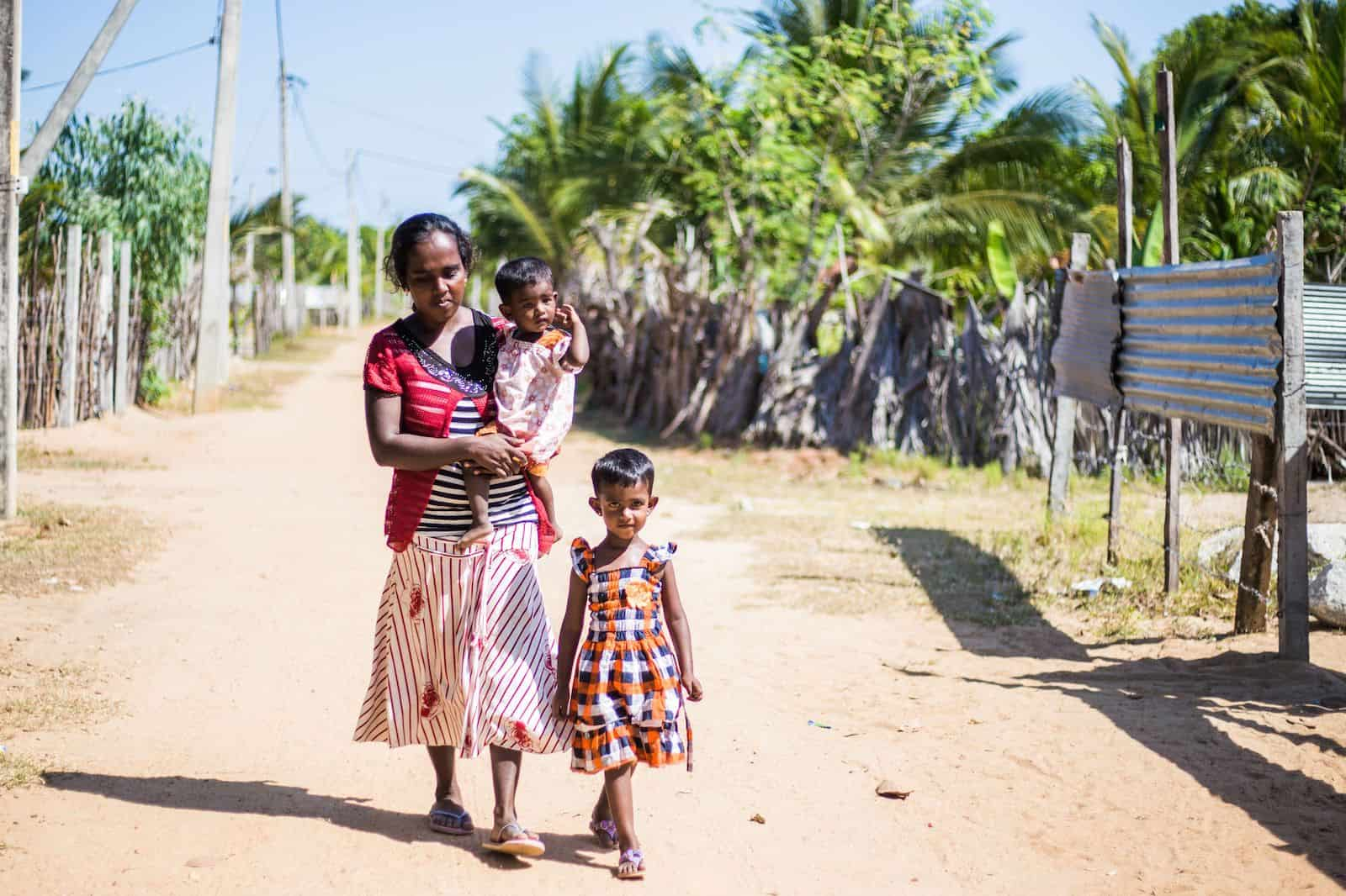 A woman holding a toddler and a girl walk down a dirt road.