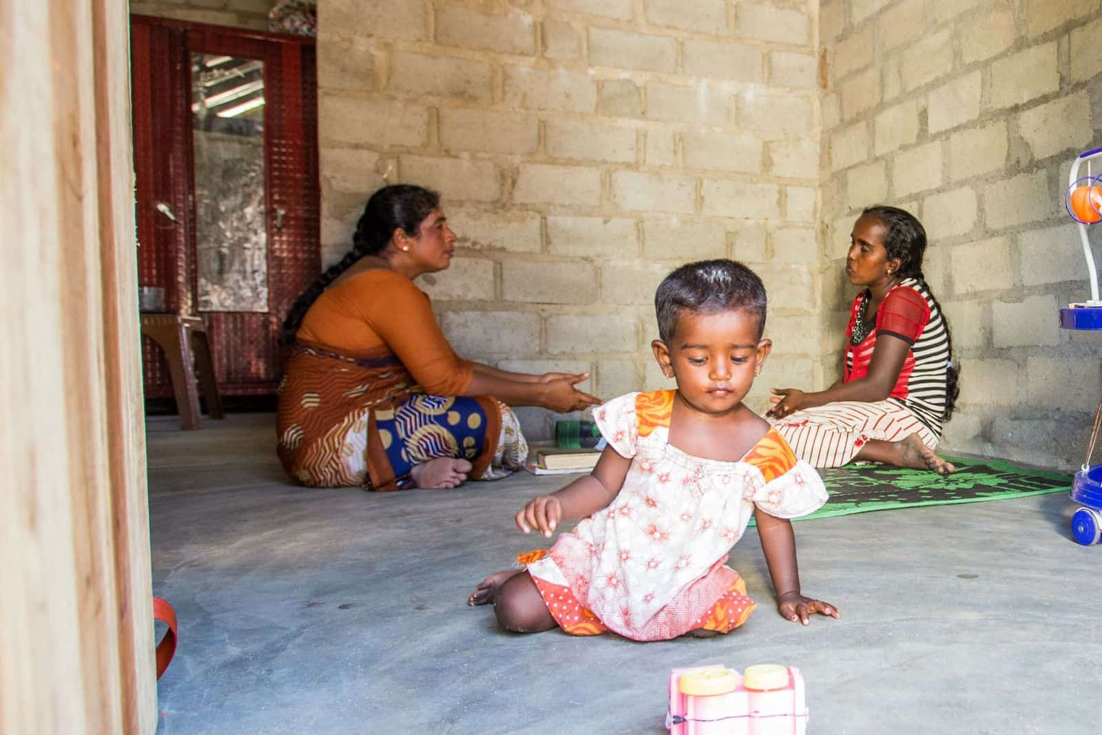 Two women sit on the floor talking with a toddler sitting on the ground.