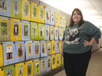 A woman in a green sweater stands in front of a wall covered in pictures of children.