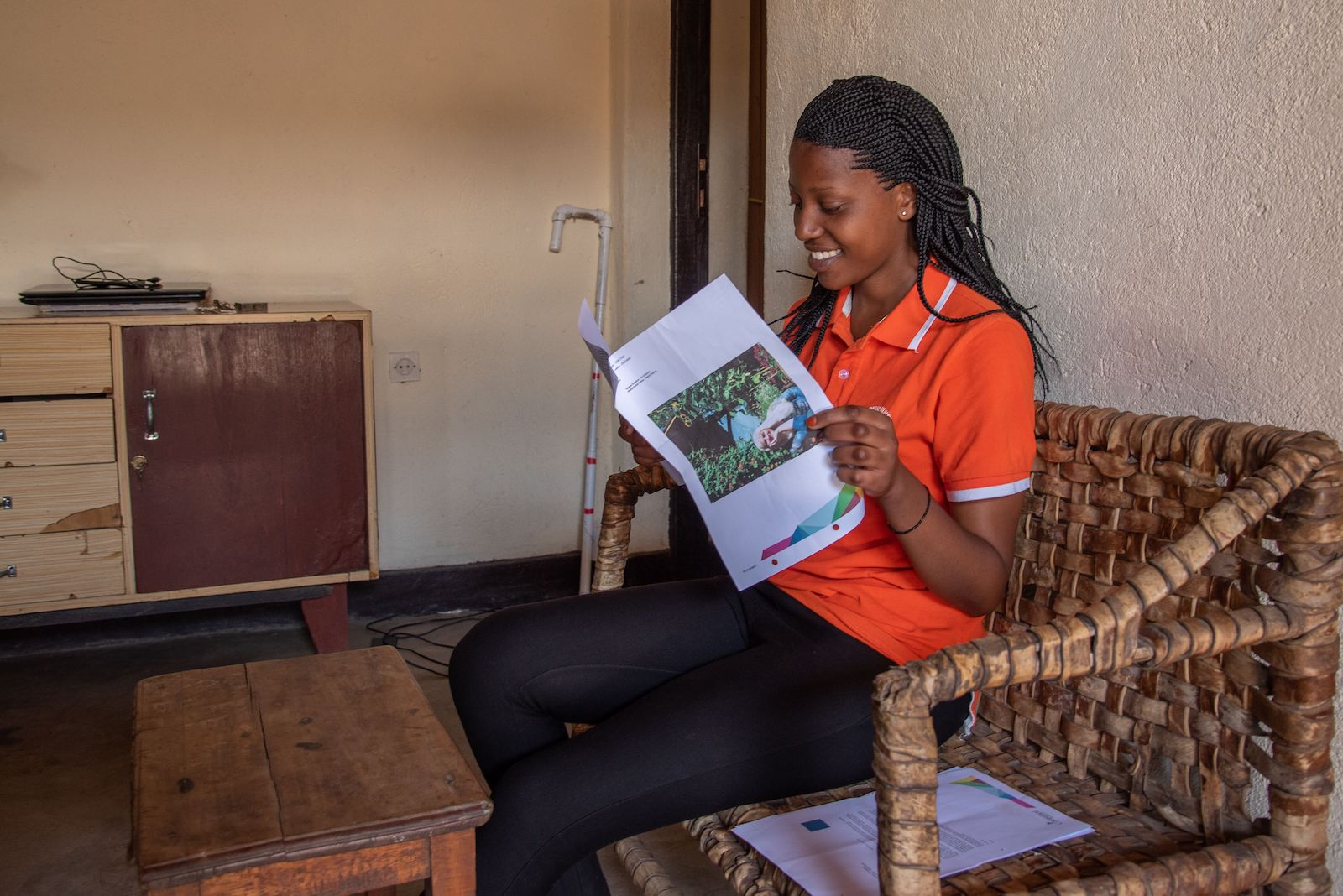 A young woman in an orange shirt sits, reading a letter.