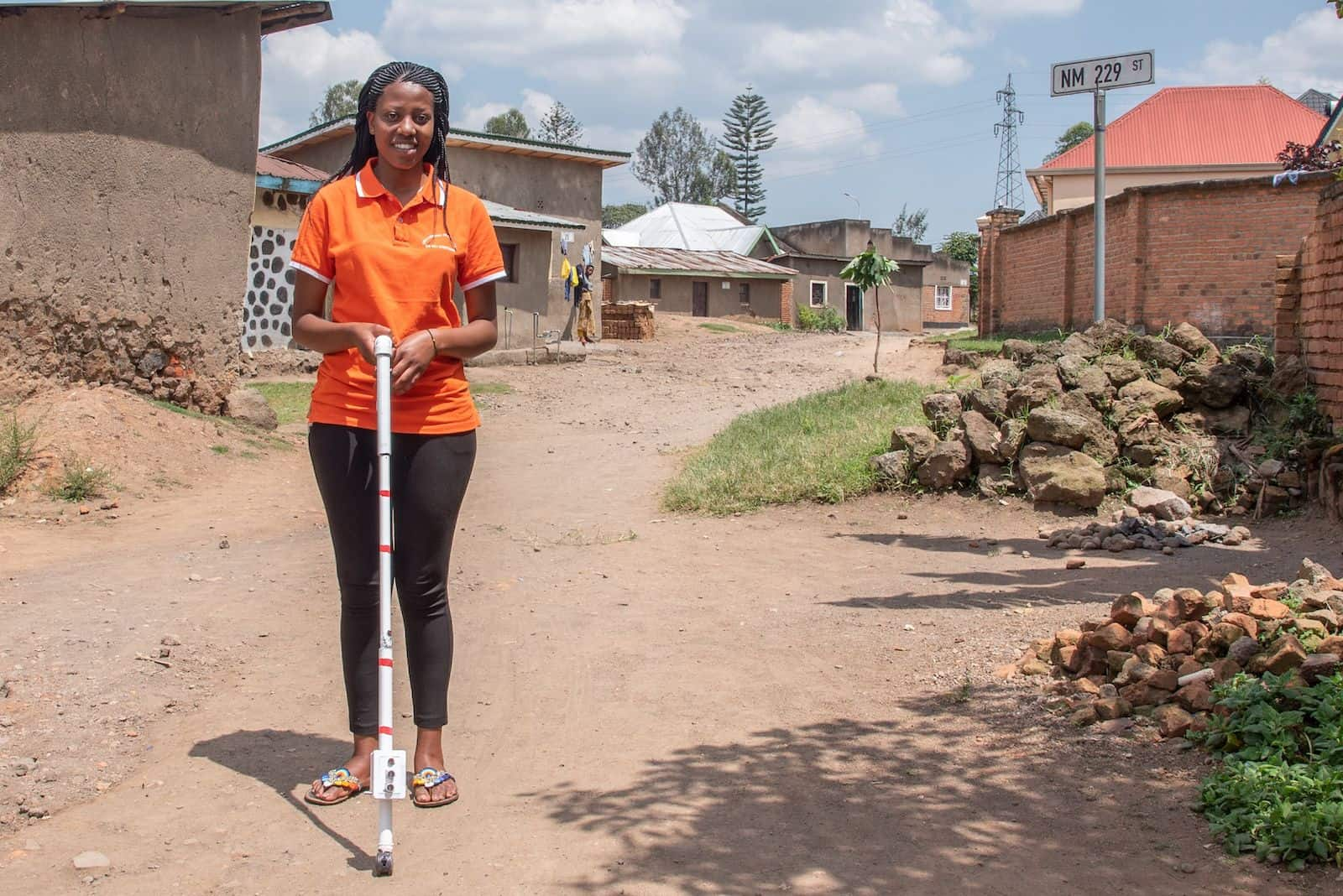 A girl in an orange shirt stands on a dirt road, holding a blind stick.