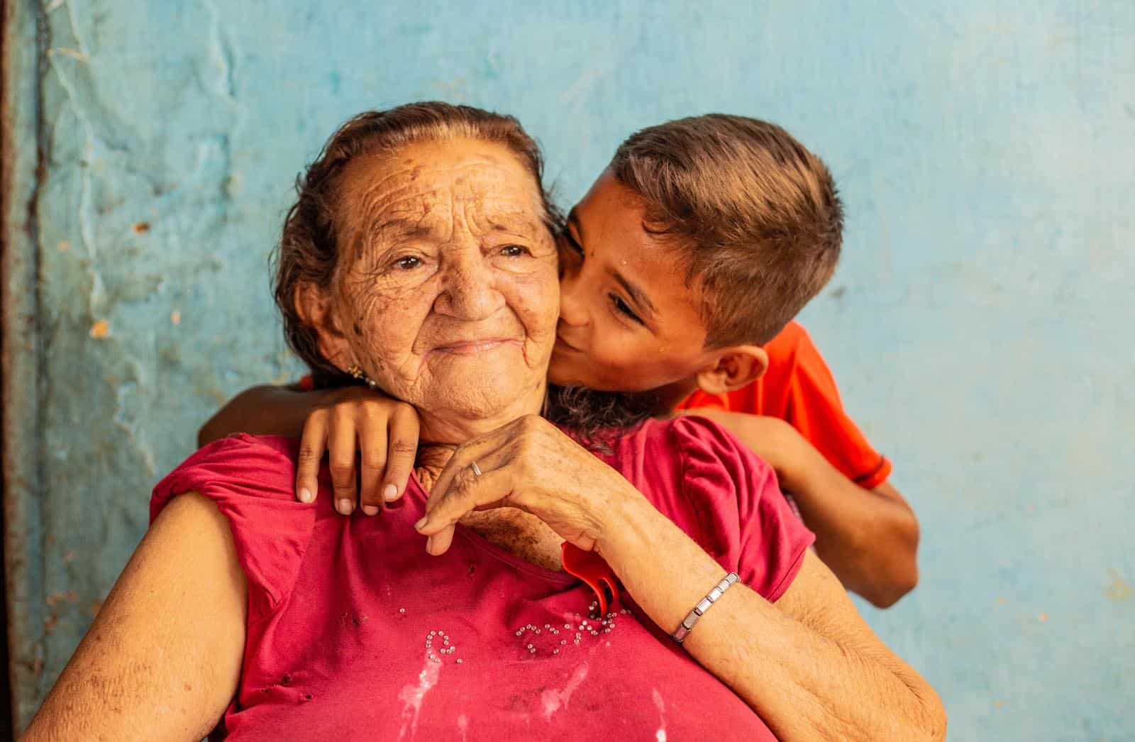A boy kisses and elderly woman on the cheek.