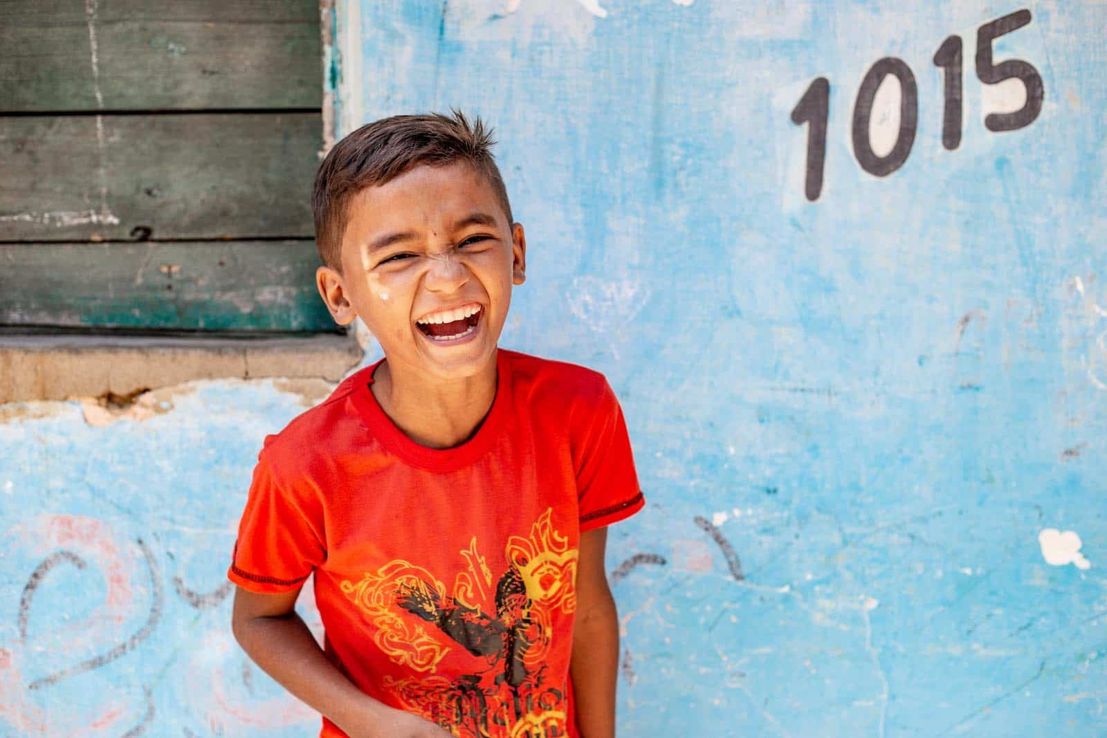 A boy in a red shirt laughs at the camera.