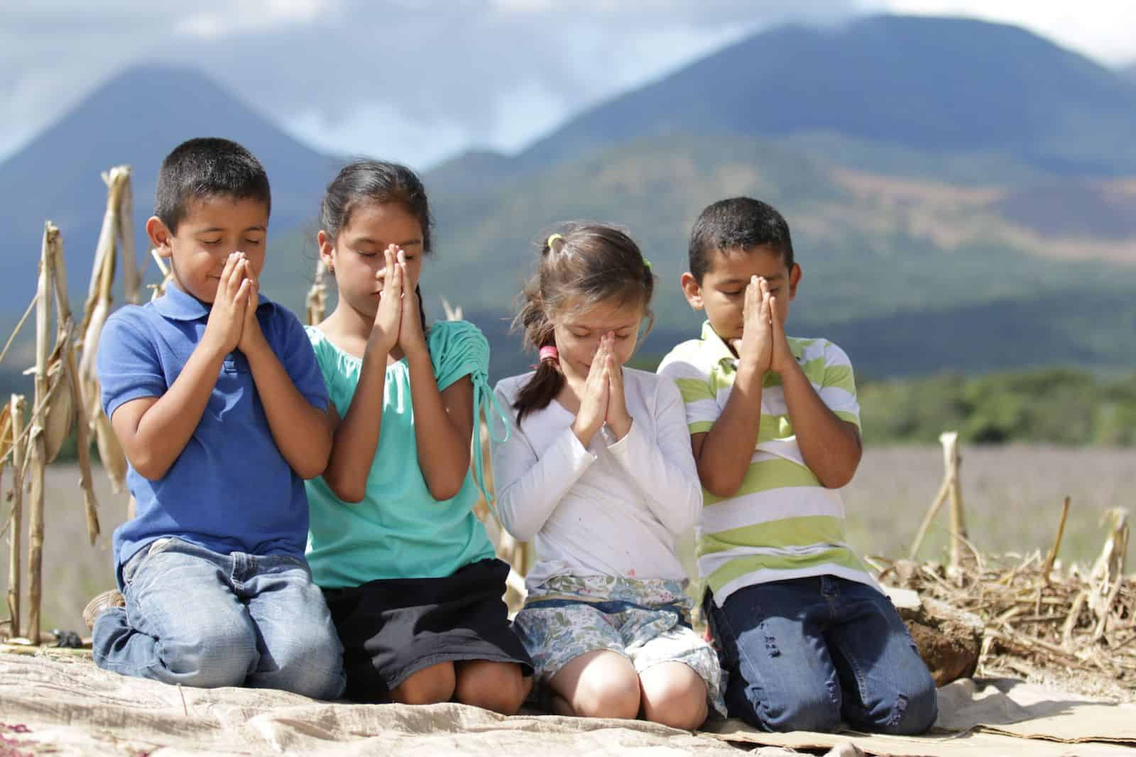 A group of four children sit outside, praying.