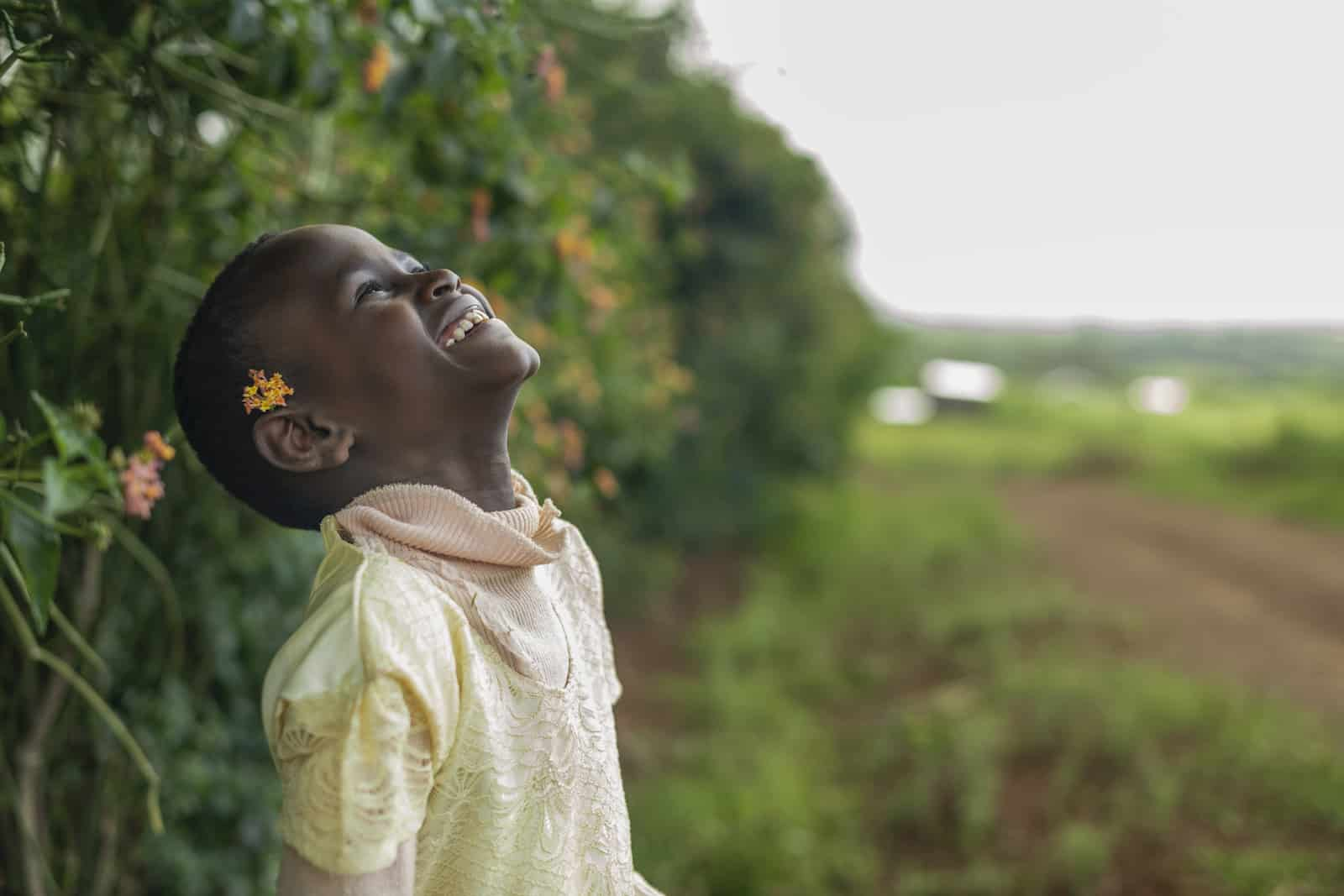 A girl throws her head back and smiles.
