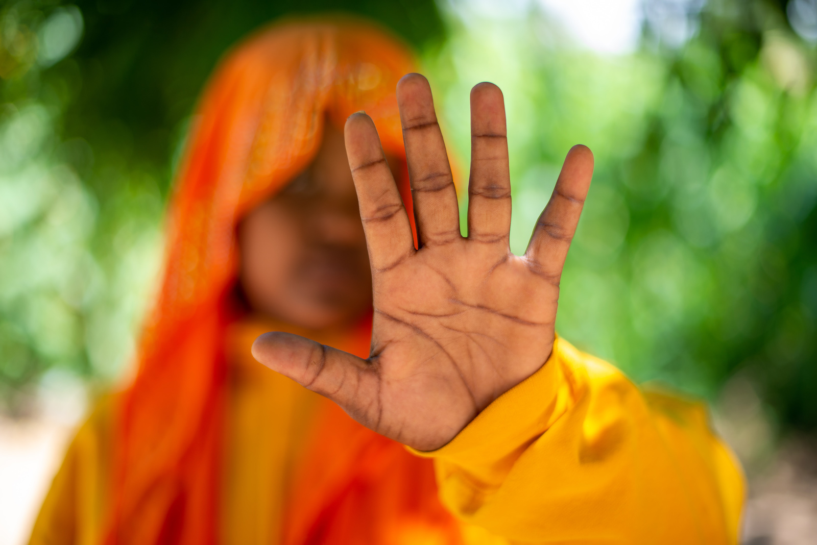 A girl in orange wearing a head covering holds her hand in front of a camera to block her face.