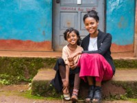 A young woman and girl sit on a front step of a church.