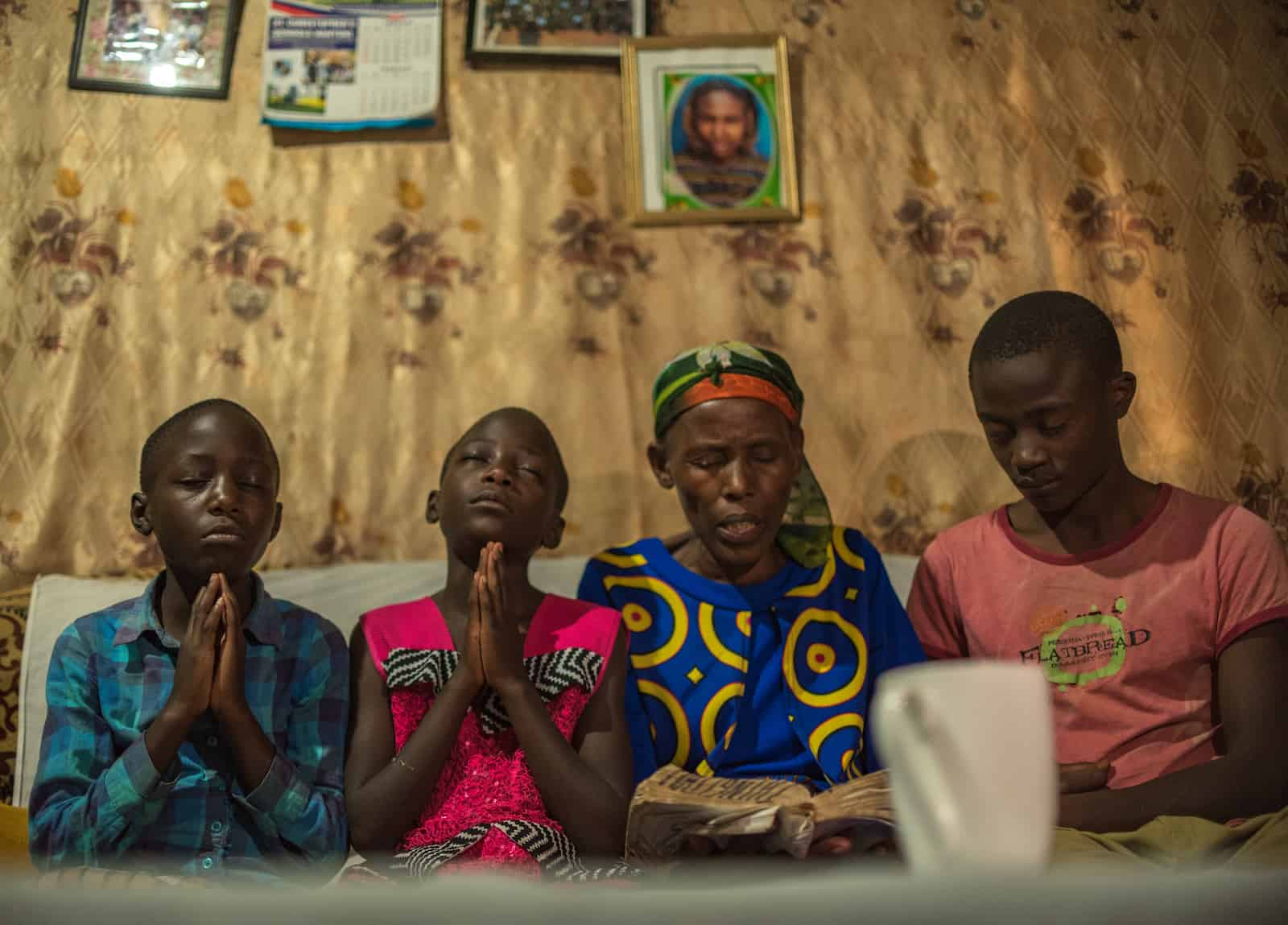 A woman reads the Bible while three children pray.