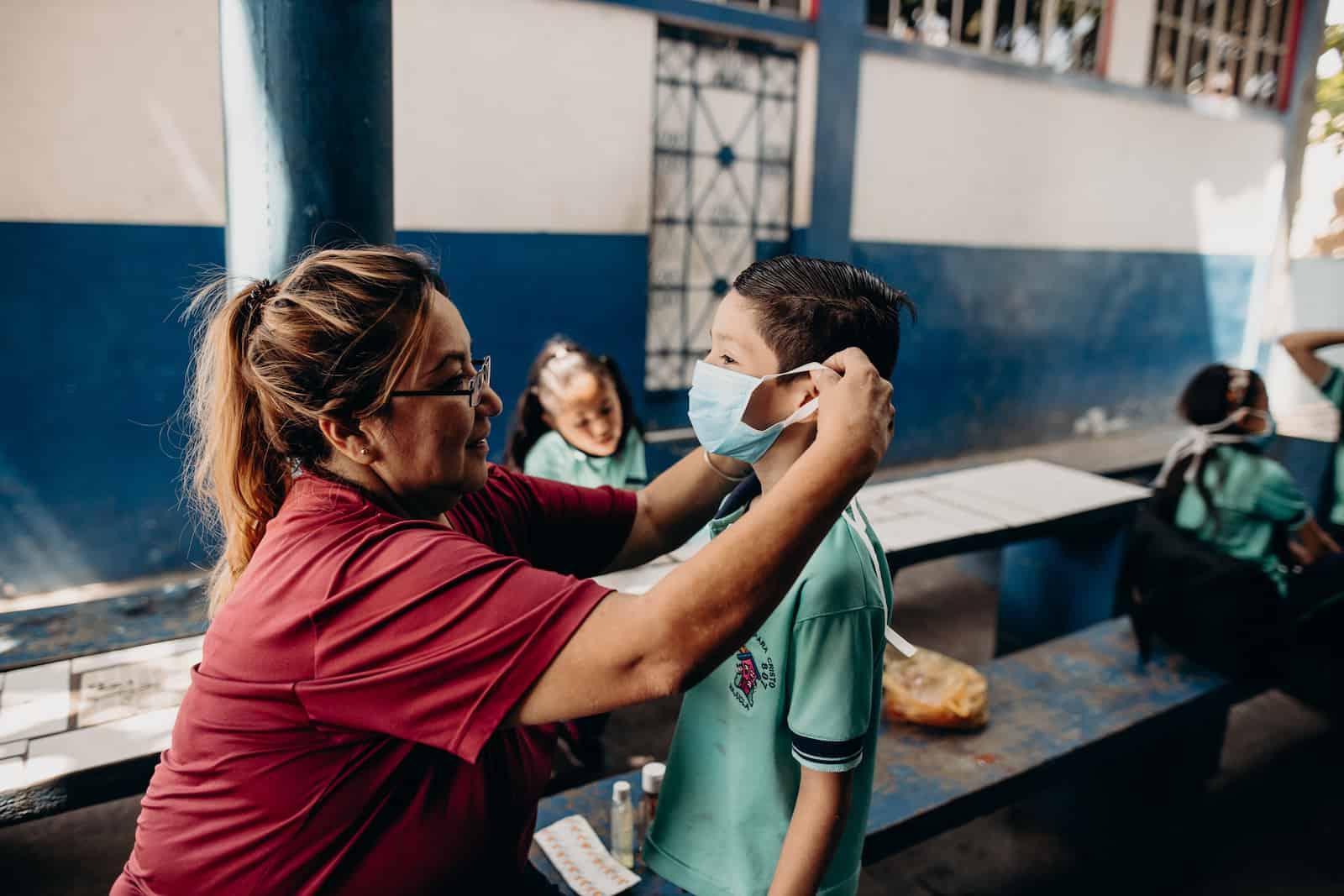 A woman secures a face mask on a boy.