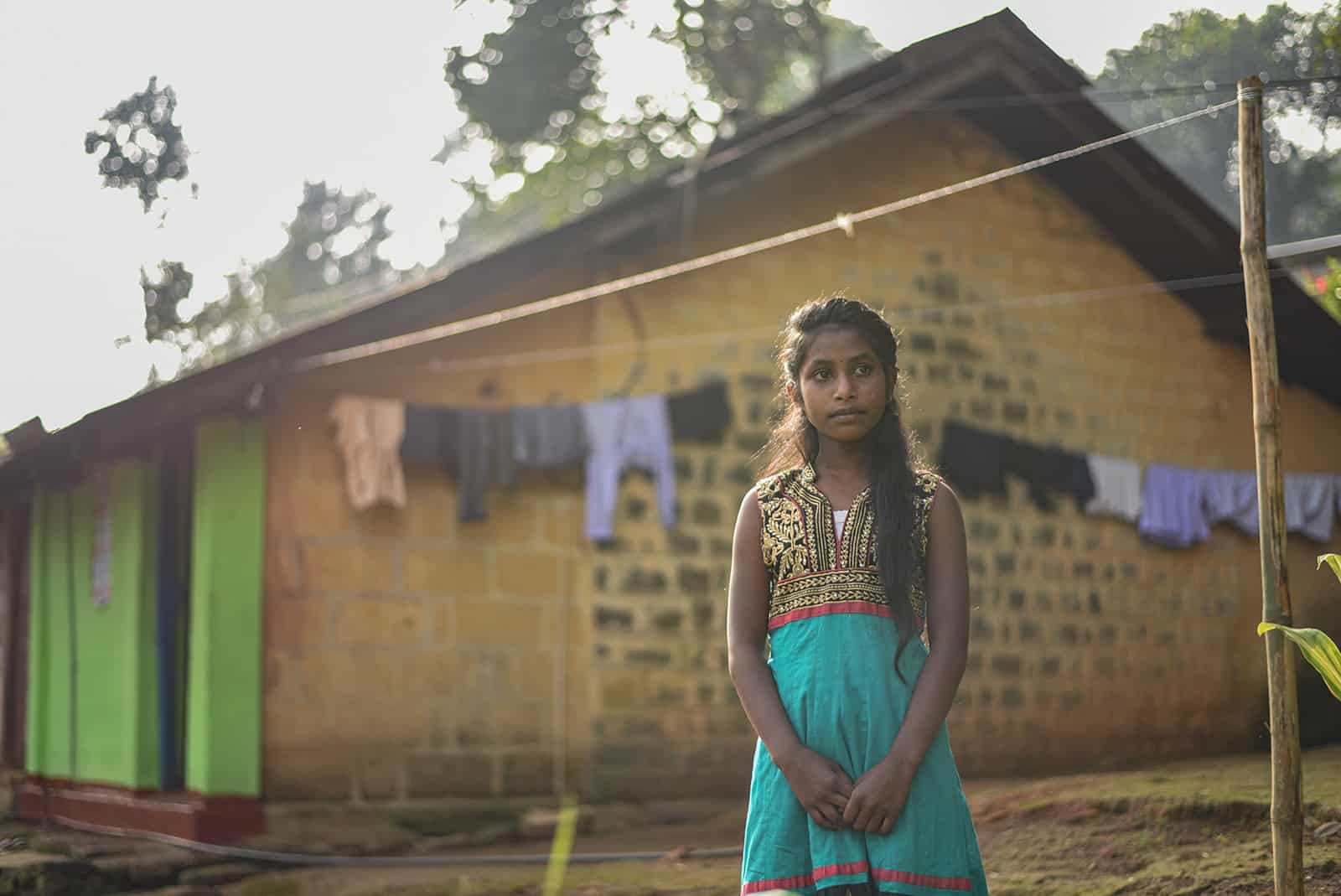 Girl standing in front of a house and clothesline