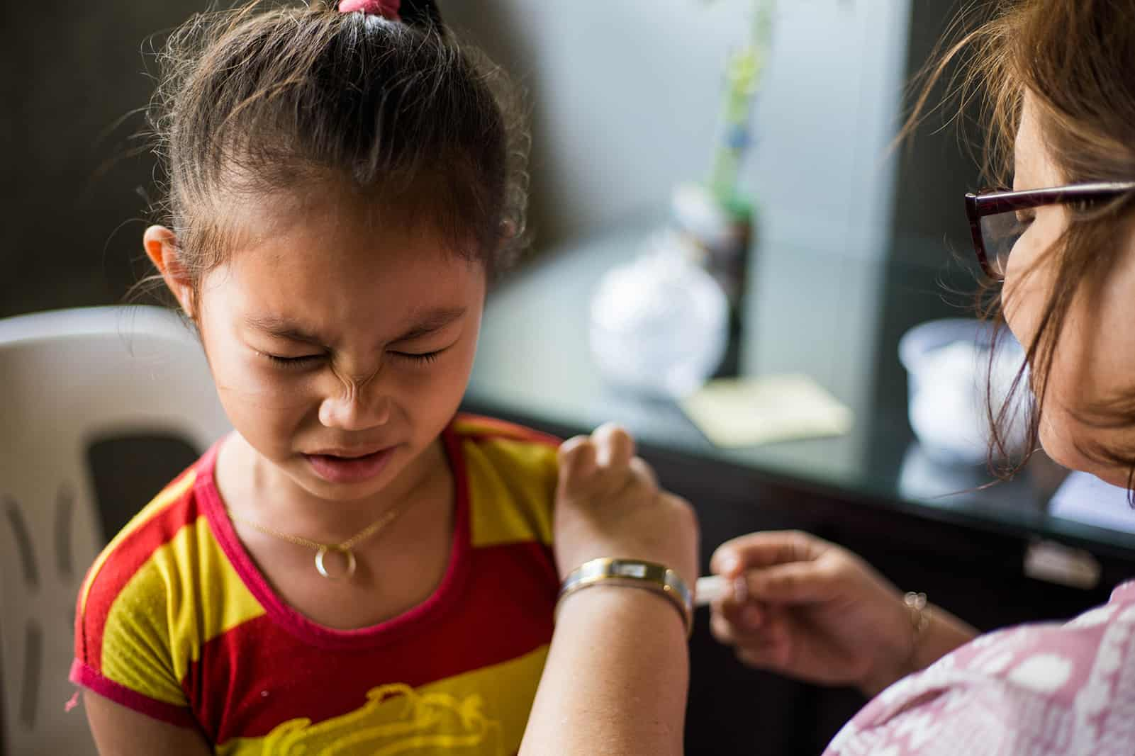 Girl wincing in pain while receiving a vaccination