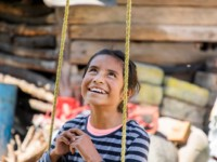A girl sits on a swing, looking up and smiling.