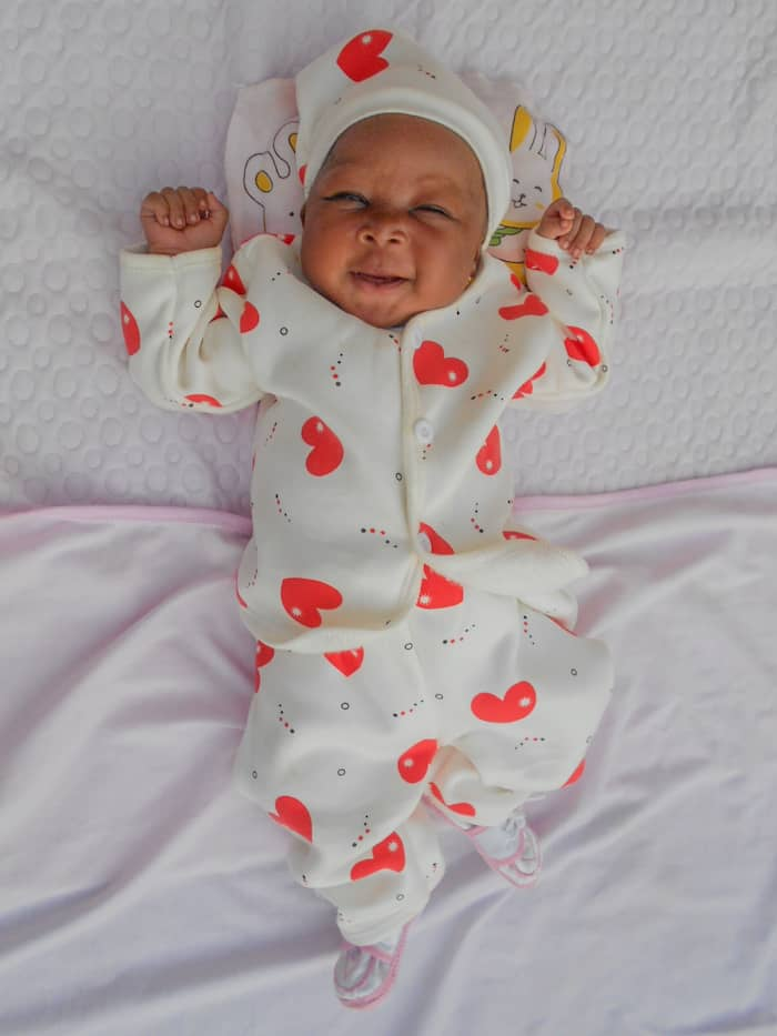 A baby on a blanket in a white and red outfit