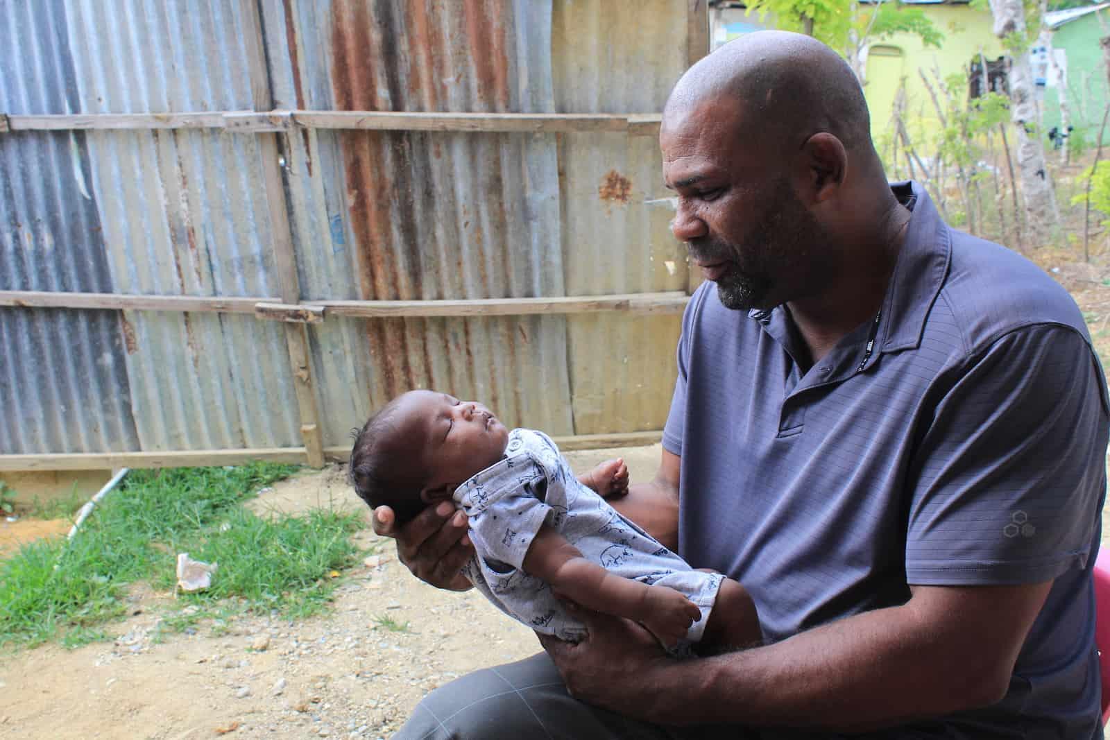 A man holds a newborn baby