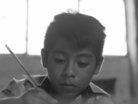 A boy holds a pencil, writing a letter.
