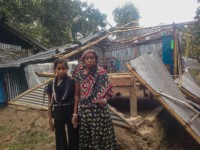 A girl and woman stand in front of a damaged home.