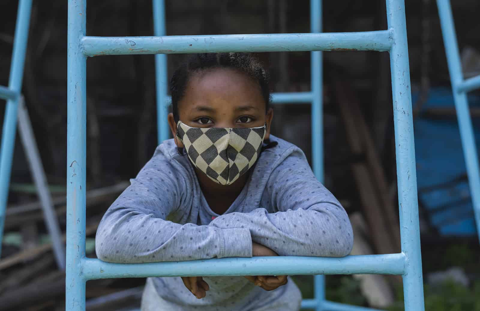 A girl with a checked face mask leans on a jungle gym.
