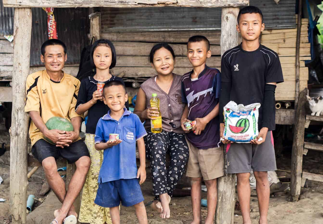 A family of six sits outside a wood home holding food.