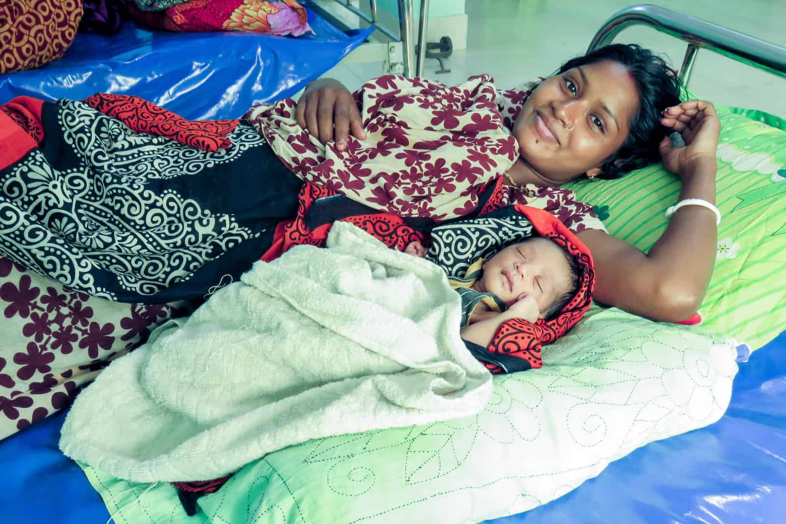 A mom and her baby lie in a hospital bed.