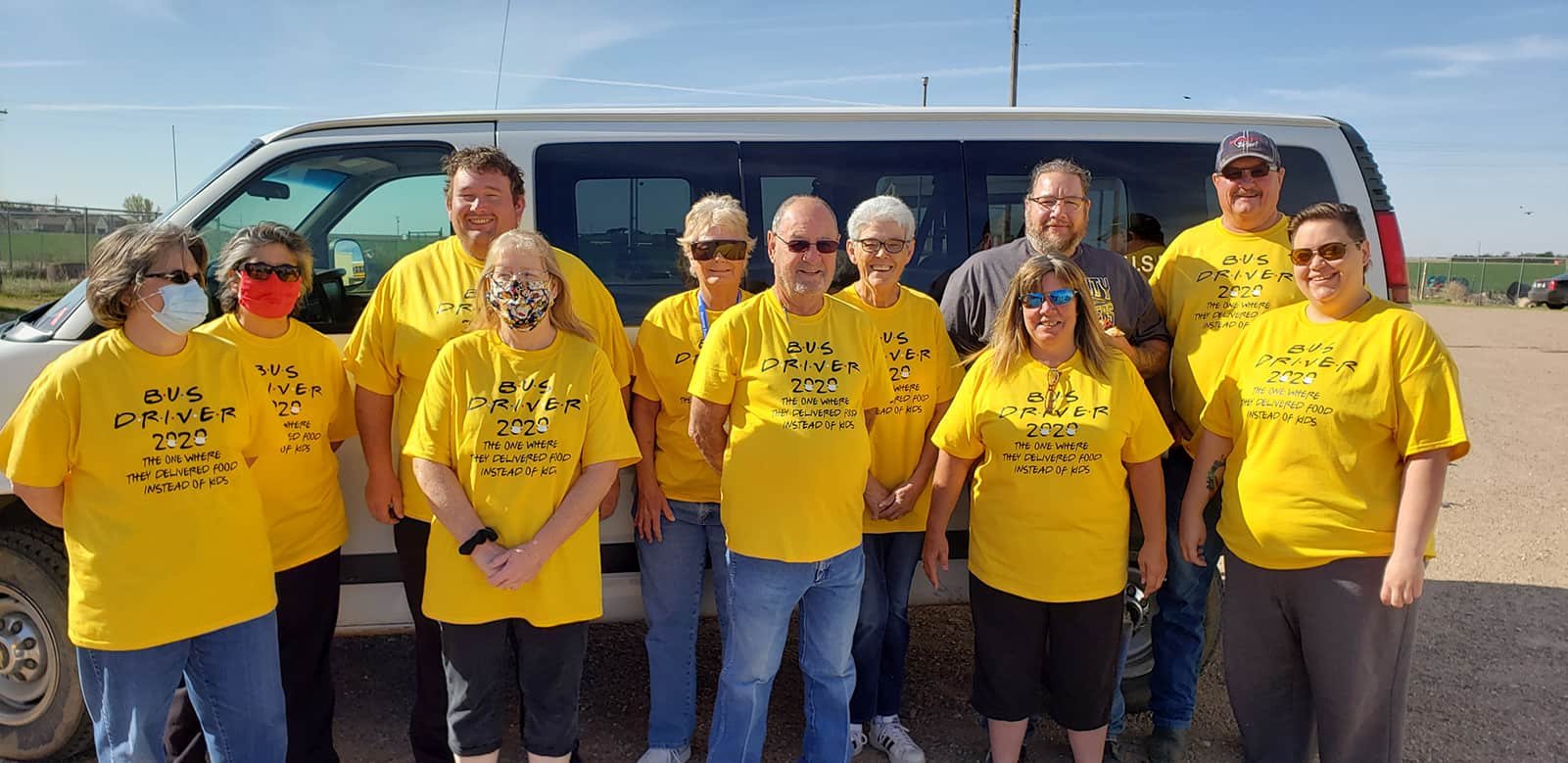Bus drivers in front of a van wearing yellow shirts