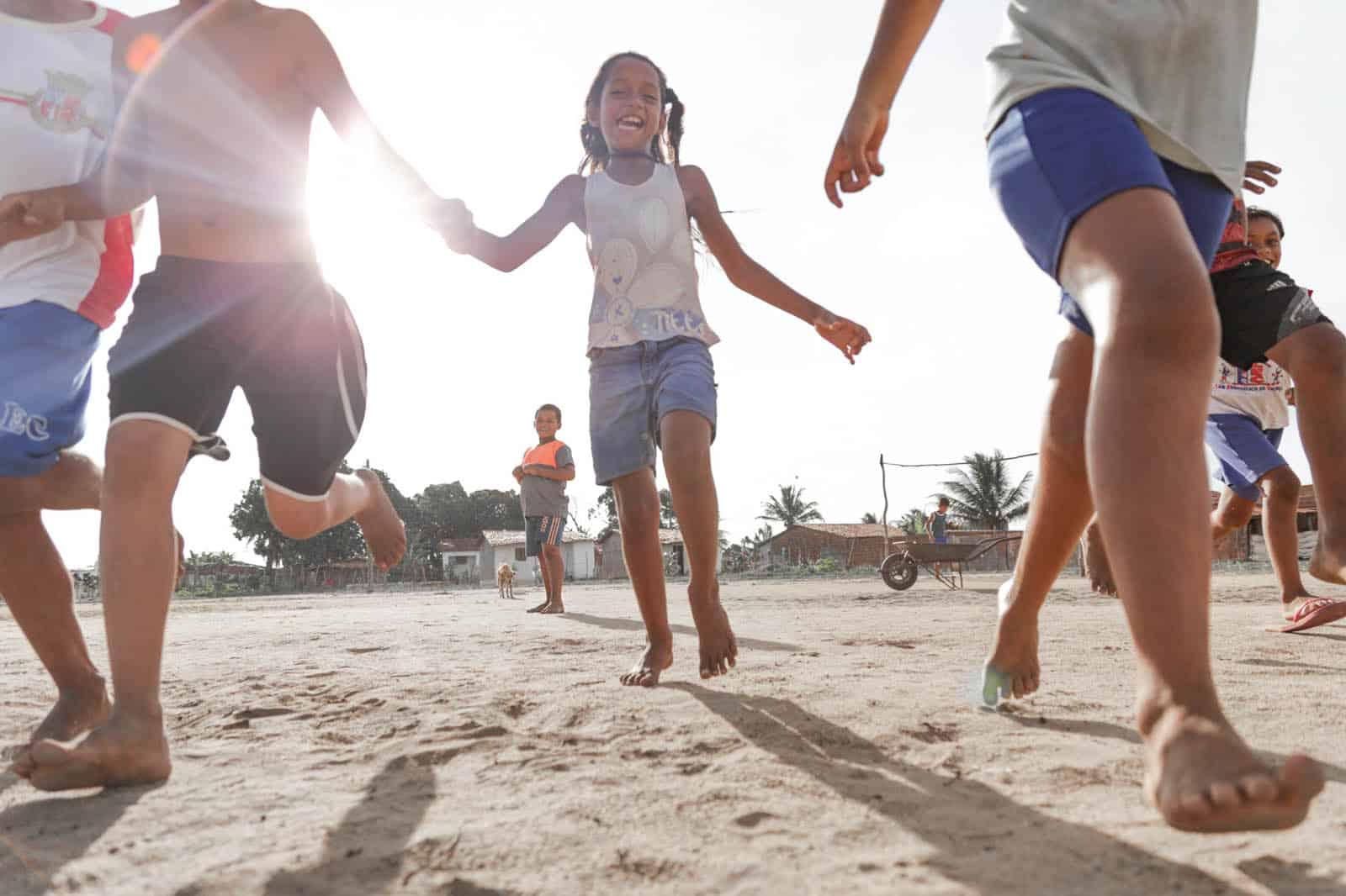 Klebiane running on sand with other children