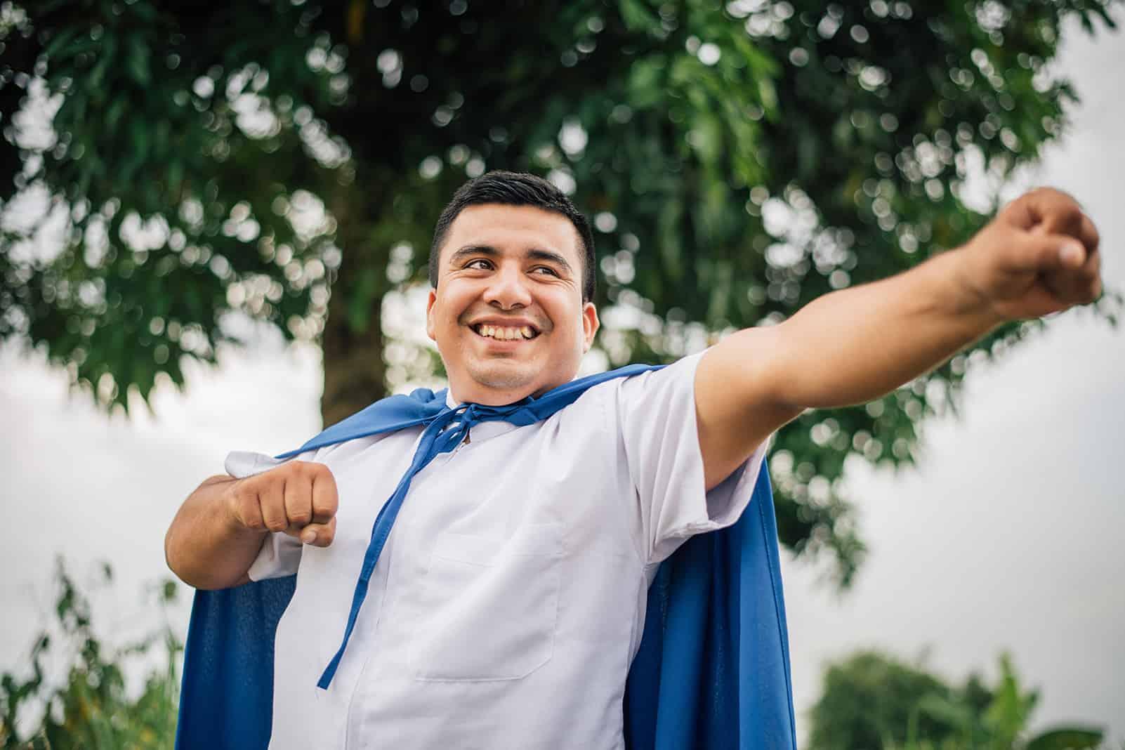 A man poses in a blue superhero cape