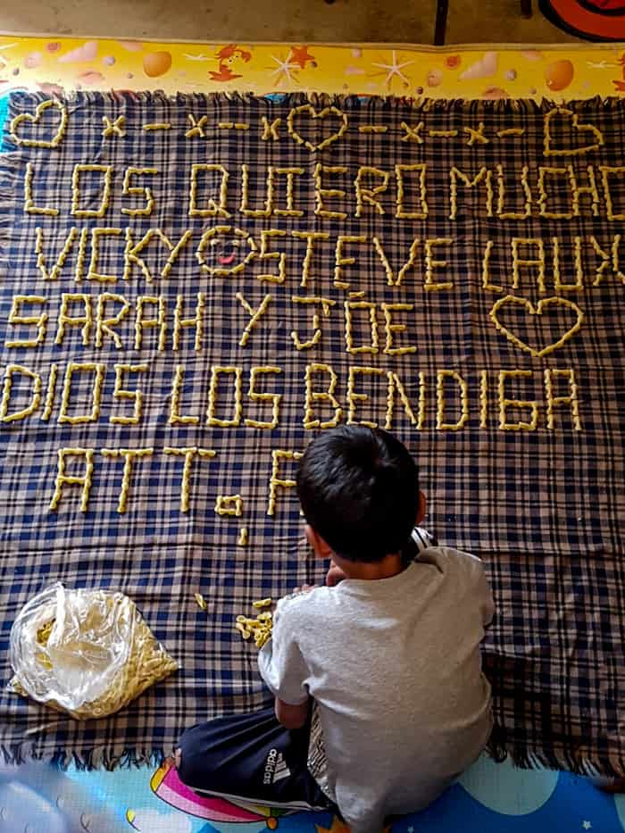 A boy makes words out of noodles
