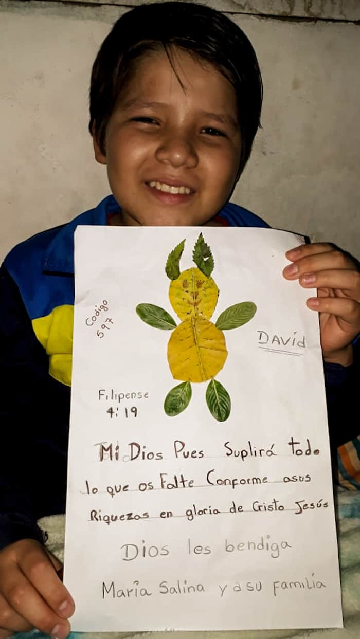 A boy holds a sign with an animal made out of leaves on it and Spanish writing.