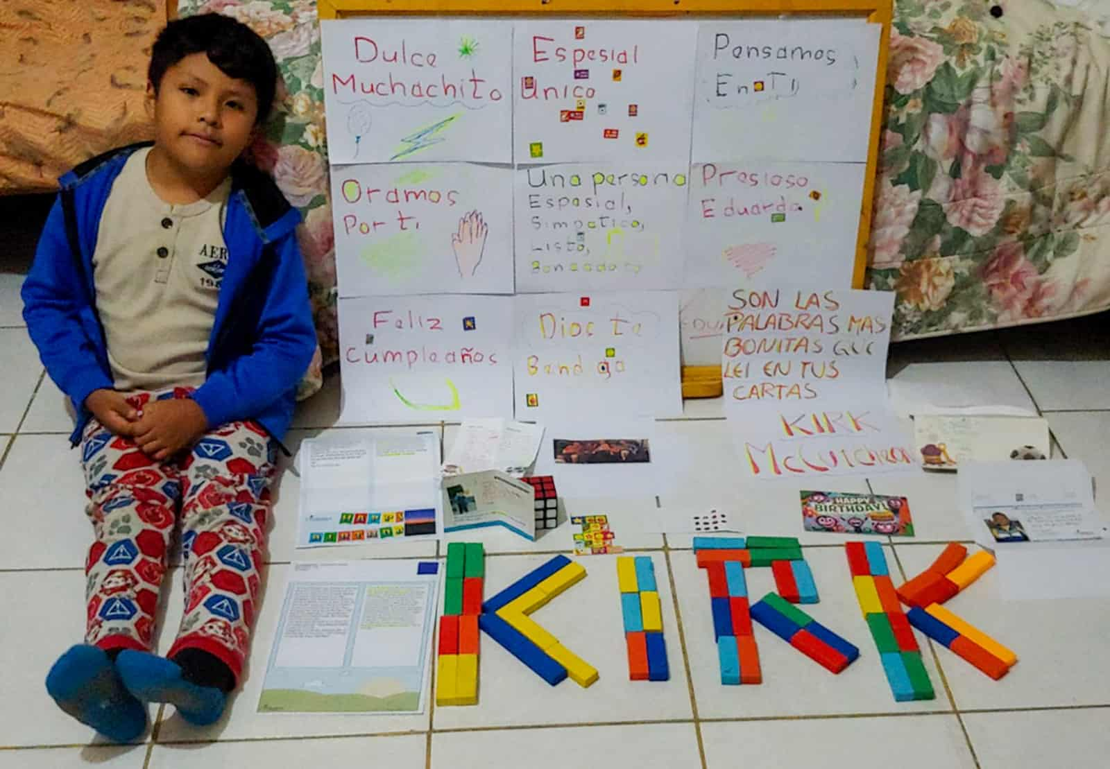 A boy sits next to posters written in Spanish