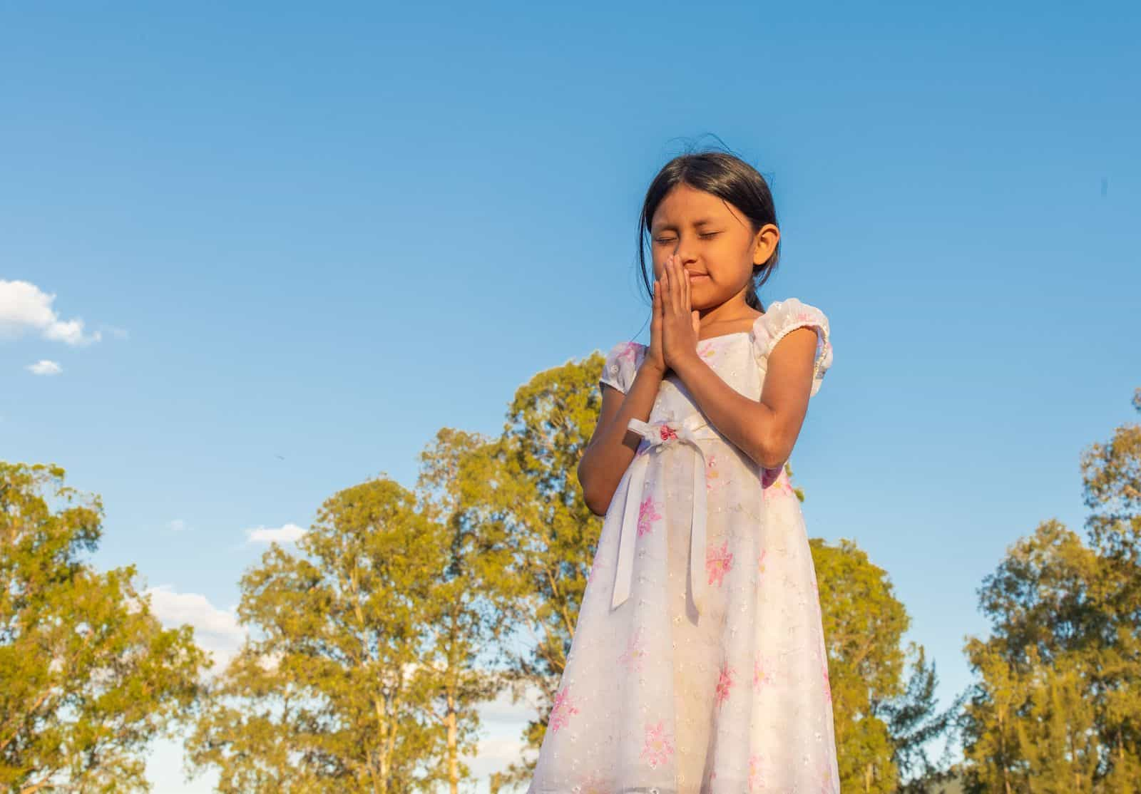 A girl prays, standing outside
