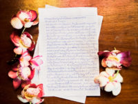 A letter written in Thai surrounded by flowers.