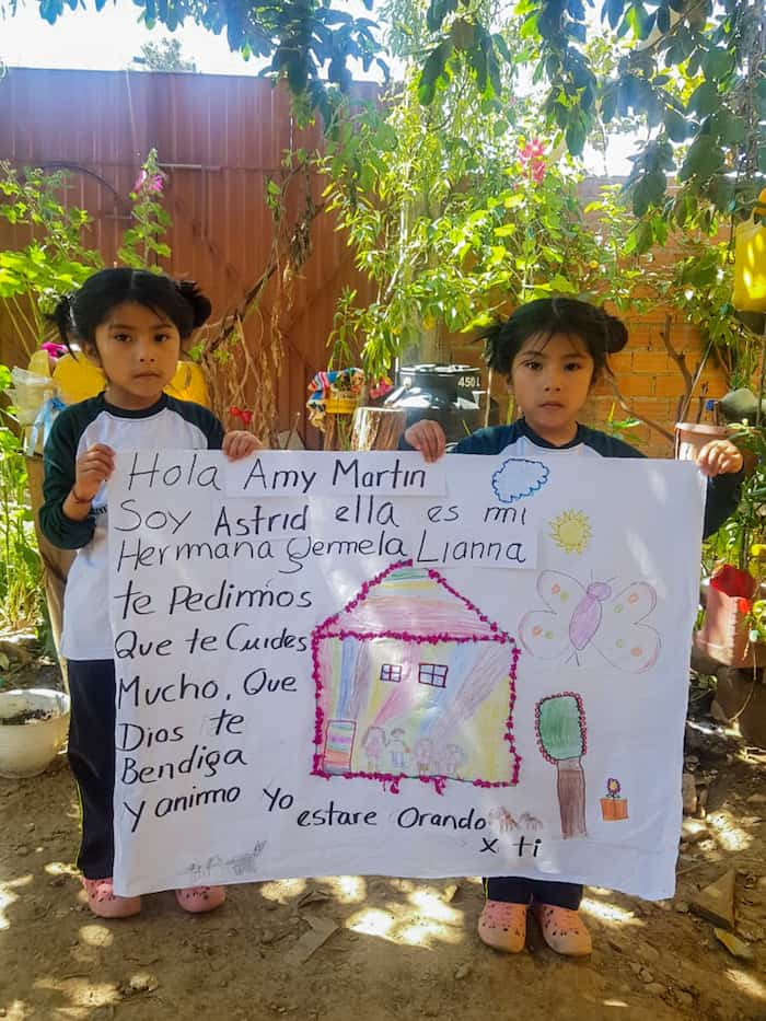 Twin girls hold up a poster with Spanish written on it.
