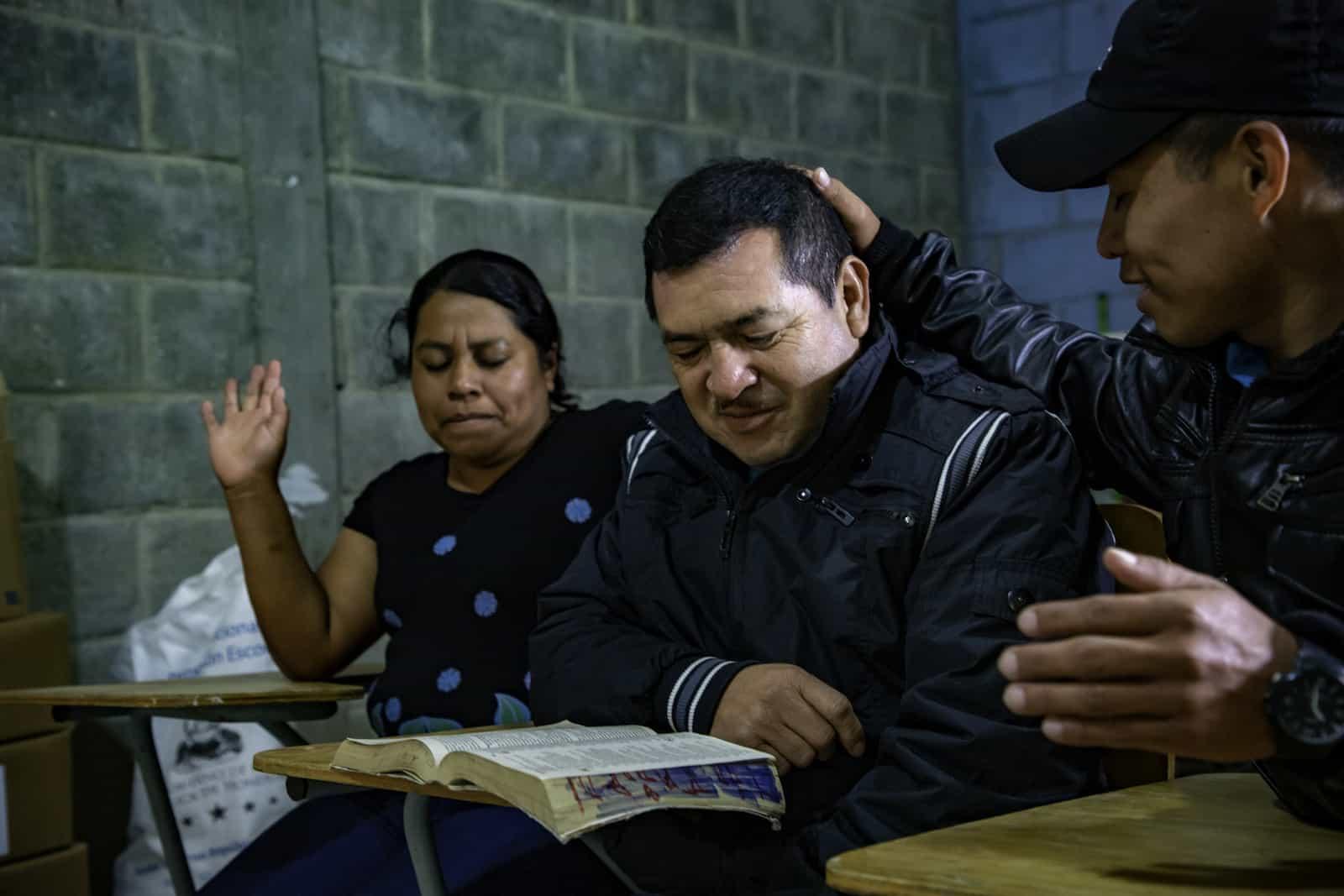 Three people sit together, praying.